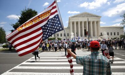 A man bearing an upside down American flag watches as protesters gather outside the U.S. Supreme Court as the court issued an immigration ruling June 26, 2018 in Washington, DC. Win McNamee | Getty Images